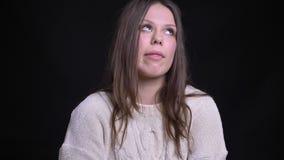 Pousse de plan rapproché de la jeune femelle caucasienne attirante faisant différentes expressions du visage et posant devant la  banque de vidéos