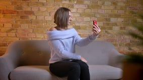 Pousse de plan rapproché de la jeune femelle caucasienne avec du charme prenant des selfies au téléphone tout en se reposant sur  clips vidéos