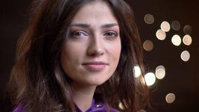 Pousse de plan rapproché de la jeune femelle caucasienne avec du charme se tournant vers la caméra avec ses cheveux flottant dans banque de vidéos