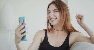 Pousse de plan rapproché de la jeune femelle caucasienne sexy dans la combinaison de noir ayant un faire appel visuel au téléphon banque de vidéos