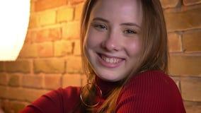 Pousse de plan rapproché de la jeune femelle dodue avec du charme se tournant vers la caméra et souriant dans un appartement conf clips vidéos