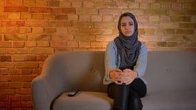 Pousse de plan rapproché de la jeune femelle musulmane attirante dans le hijab observant un film triste à la TV tout en se reposa clips vidéos