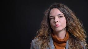 Pousse de plan rapproché de la jeune femme d'affaires caucasienne attirante étant réfléchie et regardant directement la caméra de photographie stock libre de droits