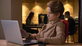Pousse de plan rapproché de la jeune femme d'affaires caucasienne attirante dactylographiant sur l'ordinateur portable et étant p photographie stock