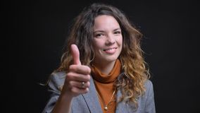 Pousse de plan rapproché de la jeune femme d'affaires caucasienne attirante faisant des gestes le pouce et souriant gaiement avec photo stock