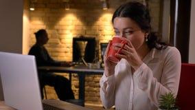 Pousse de plan rapproché de la jeune jolie femme d'affaires caucasienne ayant une pause-café devant l'ordinateur portable à l'int photos libres de droits