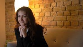 Pousse de plan rapproché de la jeune jolie TV de observation femelle caucasienne souriant avec l'excitation et la fascination tou photos libres de droits