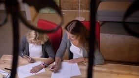 Pousse de plan rapproché de la jeune mère caucasienne enseignant à sa petite jolie fille comment dessiner à la maison confortable banque de vidéos