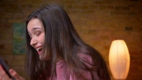 Pousse de plan rapproché de transmission de messages femelle caucasienne de jeune jolie brune sur le comprimé et du sourire heure banque de vidéos