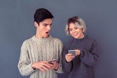 Pousse de studio de jeune homme et de femme d'isolement sur le mur gris utilisant le smartphone Photo libre de droits