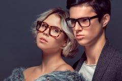 Pousse de studio de jeune homme et de femme sur la haute couture grise de mur Photos libres de droits
