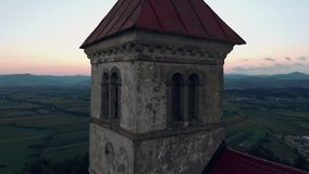 Pousse haute étroite d'antenne d'une vieille église catholique sur une colline avec une belle vue au village dans l'heure d'été d clips vidéos