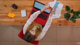 Pousse supérieure de plan rapproché du jeune employé caucasien à l'aide de l'ordinateur portable et écrivant un rappel au sujet d banque de vidéos