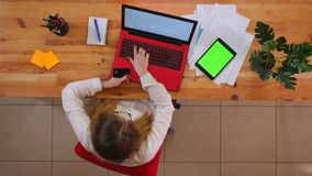 Pousse supérieure de plan rapproché du jeune employé caucasien faisant des emplettes en ligne sur l'ordinateur portable avec le c banque de vidéos
