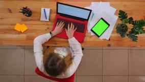 Pousse supérieure de plan rapproché du jeune employé caucasien travaillant sur l'ordinateur portable avec le comprimé avec l'écra banque de vidéos