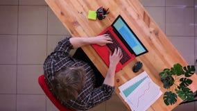 Pousse supérieure de plan rapproché du jeune homme d'affaires caucasien dactylographiant sur l'ordinateur portable sur le bureau  clips vidéos