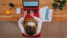Pousse supérieure de plan rapproché de jeune femme d'affaires caucasienne en verres utilisant l'ordinateur portable sur le bureau banque de vidéos