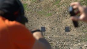 Pousses d'homme à une cible d'une arme à feu, au ralenti clips vidéos