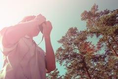 Pousses de photographe sur l'appareil-photo dans la forêt, vue inférieure Image stock