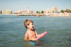 Pousses joyeuses de petit garçon d'un eau-pistolet à quelqu'un en mer Photos libres de droits