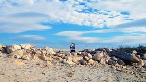 Poussette de bébé sur le bord de la mer de sable avec des nuages images stock