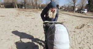 Poussette de bébé sur le sable banque de vidéos