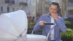 Poussette de oscillation d'homme somnolent fatigué se reposant sur le banc de parc, épuisement de condition parentale clips vidéos