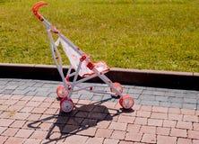 Poussette vide sur le trottoir, près de la pelouse verte plate pour les jeux des enfants photos stock