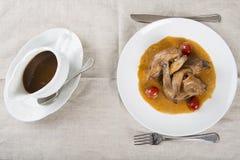 Poussin mit Traubensoße Stockfoto