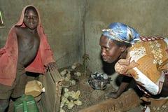 Poussins d'élevage par la femme ougandaise avec le fils Image stock