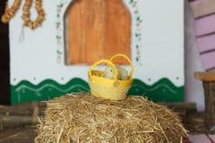 Poussins de Pâques dans le panier avec des oeufs sur une pile de foin dans la maison ukrainienne traditionnelle Image stock