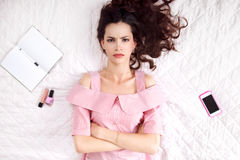 Pouted woman lying with crossed hands top view Royalty Free Stock Image