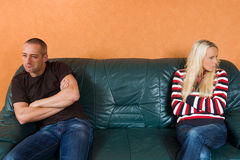 Poutful couple. Young couple sitting poutful on a sofa after a conflict Royalty Free Stock Images