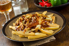 Poutine. A plate of Canadian poutine with french fries, gravy, cheese curd, and a beer Stock Photography