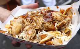 Poutine for Bastille Day Celebration in NYC. Poutine, a Quebec dish, made with grilled chicken, french fries, cheese curb and topped with light brown gravy, seen royalty free stock image