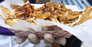 Poutine for Bastille Day Celebration in NYC. Poutine, a Quebec dish, made with grilled chicken, french fries, cheese curb and topped with light brown gravy, seen Royalty Free Stock Photos