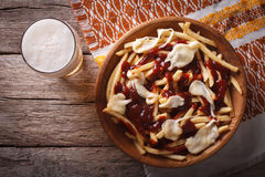 Poutine and beer close-up. horizontal top view Stock Photography
