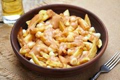 Poutine Canadees traditioneel snel voedsel met gebraden gerechten, kwark, jus stock afbeeldingen