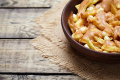 Poutine Canadian homemade traditional fast food meal with fries. Curd cheese, gravy and beer on vintage wooden table background. Empty space for design text Stock Photo