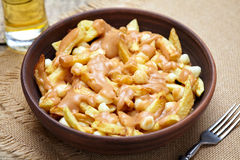 Poutine Canadian traditional fast food with fries, curd cheese, gravy. Poutine Canadian traditional fast food with fries, curd cheese and gravy on vintage wooden Stock Images