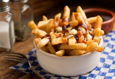 Poutine. Classic French Canadian poutine with french fries, gravy, and cheese curds on a rustic tabletop Royalty Free Stock Photography
