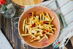 Poutine dłoniaki na czerni powierzchni Kanadyjski naczynie z grulami, serem i kumberlandem, zdjęcia stock