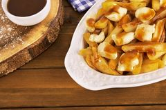 Poutine plate on a wooden background. Cooked with french fries, gravy and curd cheese. stock photo