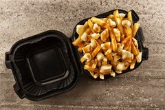 Poutine in a takeout container. royalty free stock photography