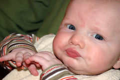 Pouting Baby. Baby with a pout because he is eating (something not so tasty Royalty Free Stock Photos