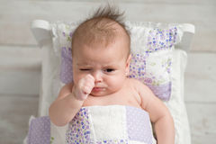 Pouting Baby Girl in Tiny Bed stock images