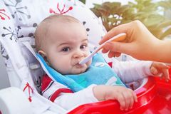 Pouting baby have lunch at the table in a suny day stock image