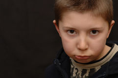 Pouting boy. Pouting boy looks at the camera with a down-turned lip. Copy space. Horizontal orientation royalty free stock photos