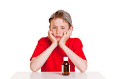 Pouting boy with medication bottle Stock Photo