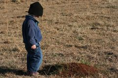 Pouting child. Toddler in a field looking at ant mound pouting stock photo